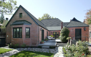 Custom marched masonry can be seen in this exterior elevation. Portions of the old bricks were handpicked, saved &. Used for the new application in order to maintain continuity. The existing synthetic deck was salvaged & modified to reduce cost while still providing a great finished look. The black windows, trim & roofing on this cottage style home give the perfect contrast to the brick exterior. A new high efficiency condenser discretely placed near the fence line, provides ample cooling while saving energy.