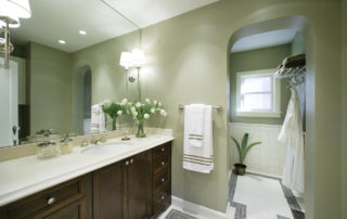 A frameless Hickory stained vanity was finished with a travertine counter top. Matching travertine was used as the bench surface inside the steam shower. A full wall vanity mirror was used to increase the appearance of space & decorated with polished nickel wall sconces. The archways are used throughout the hath to match the other areas of the home.