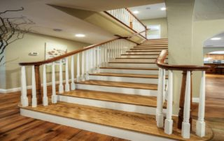 "This amazing staircase illustrates craftsmanship at it's finest. Flared bottom steps and the combination of painted/stained materials provide a grand entry to the new second story. The ""reclaimed"" sand and finish hardwood floor has narrow strips with varied species and color that result in unique beauty."