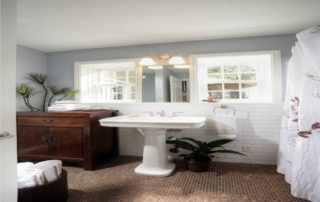 This first floor hall bathroom blends authenticity and creative design in spectacular fashion. Subway tile wainscoting, pedestal sink and a furniture style vanity are just fitting for this 1940's home. While the floor laid with pennies is brilliantly stunning.
