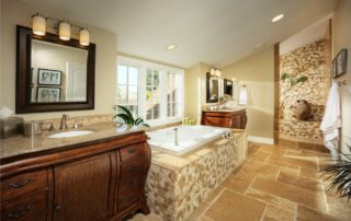 "The vaulted ceiling, layout of room and natural stone throughout make this a truly breathtaking master bathroom. The stone floor has a ""chiseled"" edge and is laid in a unique pattern. Notice the hand placed natural stone ""mosaic"" on the tub landing, as well as in the shower. A jetted soaker tub with the massage and champagne feature sits between matching his/hers furniture style vanities. Brushed nickel plumbing fixtures provide a discreet and elegant finishing touch to a master bathroom well deserved by this amazing couple!"