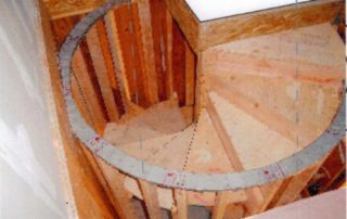 Notice the steel radius track to ensure a true circle integrated with wood posts and steps for structural soundness.